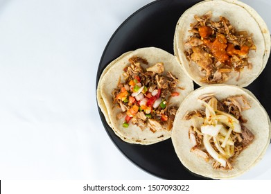 Mexican carnitas tacos, slow cooked pulled pork, traditionally from the state of Michoacán and made famous by the towns of Quiroga and Uruapan. Served with onion, salsa banderita and spicy chili sauce