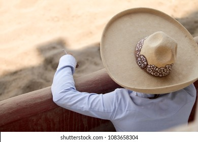 A mexican charro with his sombrero smoking a cigarette while watching another charros