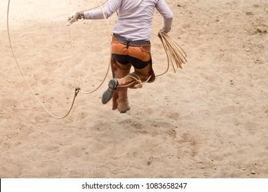 mexican charro jumping through his lasso, charreria, charreada