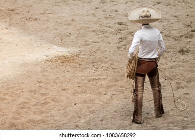 Mexican charro standing in the arena, charreria, mexican charro hat