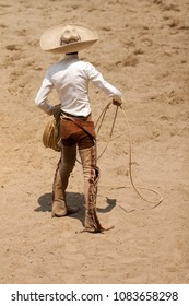 Mexican charro standing bravely holding his lasso with right hand