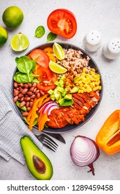 Mexican chicken burrito bowl with rice, beans, tomato, avocado,corn and spinach, white background. Mexican cuisine food concept.