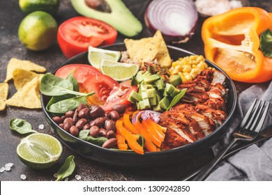 Mexican chicken burrito bowl with rice, beans, tomato, avocado,corn and spinach, dark background. Mexican cuisine food concept.