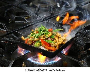 mexican chicken fajitas on sizzling plate with fire and smoke