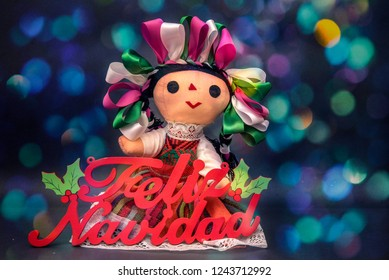 Mexican Christmas doll with colorful sign and ribbons in bright lights background