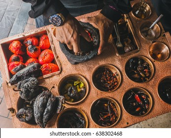Mexican cooks salsa in a traditional stone bowl Molcajete, metallic table with condiments and roasted peppers and tomatoes on a background. Mexican restaurant. Side view, horizontal photo