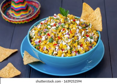 Mexican corn appetizer Elote.  Roasted street corn salad or dip with сilantro, lime, cheese, mayonnaise and chili served with chips.