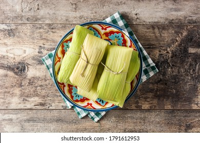 Mexican corn and chicken tamales on wooden table. Top view