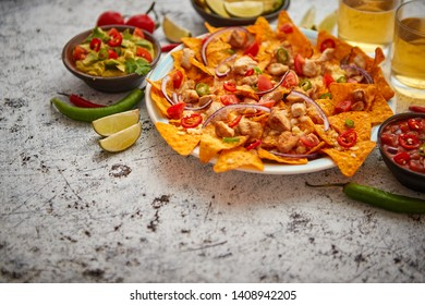 Mexican corn nacho spicy chips served with melted cheese, peppers, tomatoes, beer and side salsas.
