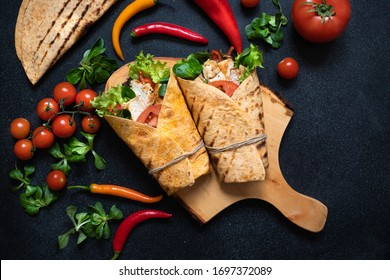 Mexican corn tortilla wrap with grilled chicken and fresh vegetables served on a wooden cutting board. Dietary healthy dish. Black background, flat lay, copy space