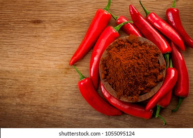 Mexican cuisine and spicy food concept with close up on fine ground red pepper powder in a wooden bowl surrounded by a bunch of hot chilli peppers on a wood background with copy space