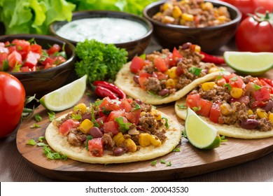 Mexican cuisine - tortillas with chili con carne and tomato salsa on wooden board, horizontal