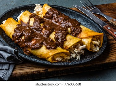 Mexican cuisine. Traditional Mexican chicken enchiladas with spicy chocolate salsa mole poblano. Enchiladas with sauce moole from Puebla, Mexico.