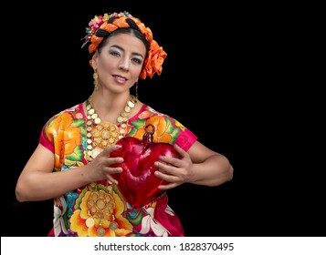 Mexican dancer from Oaxaca Mexico, wearing a costume from the region of the isthmus of Tehuantepec, dances in the guelaguetza de, with a black background and a hand embroidered dress, carries a heart