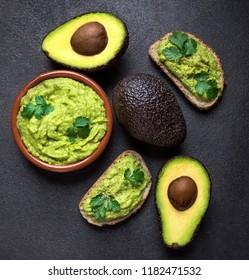 Mexican Dip Sauce Guacamole with avocado  in a clay bowl  on black background. Avocado spread. Top view. Copyspace