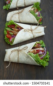 Mexican dish.Wrapped burrito with chicken and vegetables close-up on a wooden background. Space for text.