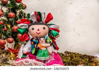 Mexican doll with colored ribbons and little girl hanging, christmas background with tree and spheres, white space for text