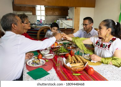 A Mexican family toasting and celebrating at a mexican party at home