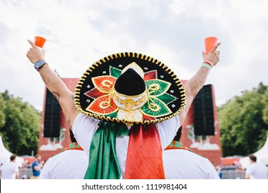 Mexican fans in uniform and sombrero are happy for their team. Horizontal