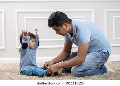 mexikanischer Vater zieht Schuhe an Sohn an