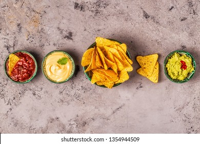 Mexican food background: guacamole, salsa, cheesy sauces with nachos, top view.