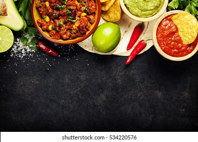 Mexican food concept: tortilla chips, guacamole, salsa, chilli with beans and fresh ingredients over vintage rusty metal background. Top view