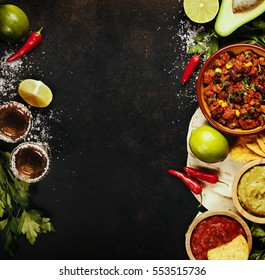 Mexican food concept: tortilla chips, guacamole, salsa, chilli with beans, tequila shots and fresh ingredients over vintage rusty metal background. Top view