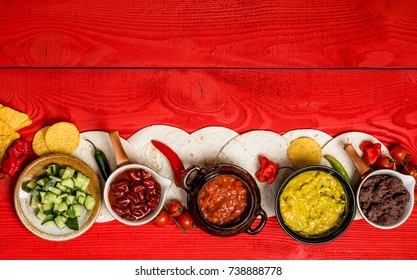 Mexican food concept: tortilla chips, guacamole, salsa, chilli, refried black beans, and fresh ingredients over vintage red rustic wooden background. vegetarian. Top view