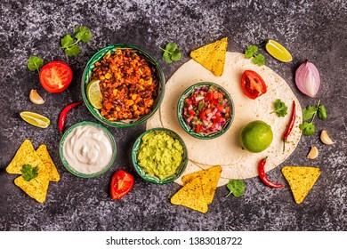 Mexican food concept: tortillas, nachos with guacamole, salsa, chili con carne, top view.