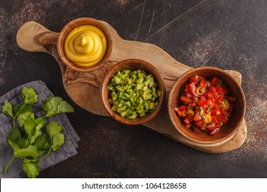 Mexican food concept. Various sauces to nachos or tacos in wooden bowls: guacamole, cheese sauce, pico del gallo