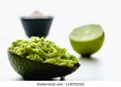 Mexican food, green guacamole sauce in avocado peel, healthy eating concept