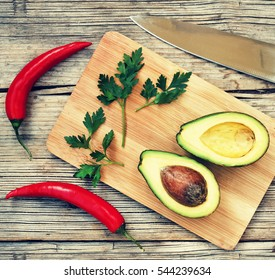 Mexican food. Ingredients for cooking nachos. Fresh vegetables on the kitchen blackboard. Avocado, Parsley, the cilantro, hot chili pepper.