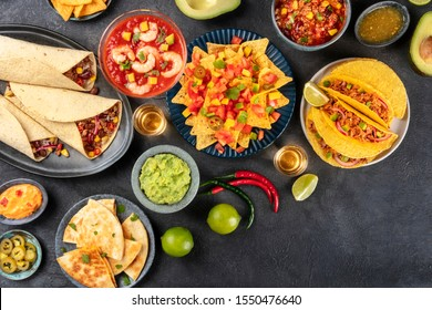 Mexican food, many dishes of the cuisine of Mexico, flat lay, overhead shot on a black background with copy space. Nachos, tequila, guacamole, burritos, quesadillas, tacos