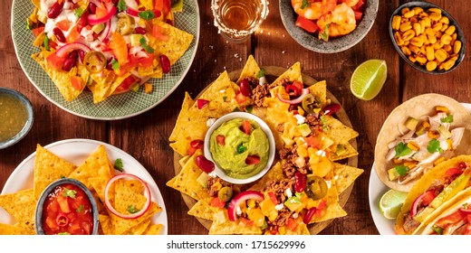 Mexican food panorama, shot from above on a rustic wooden background. Nachos, guacamole, tequila, tacos, a flat lay