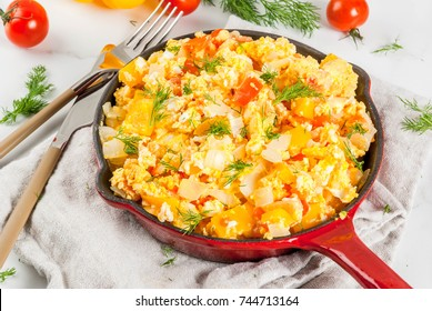 Mexican food recipes, Revoltillo de Huevos, Scrambled Eggs a la Dominicana, in portioned skillet, on white marble table,copy space