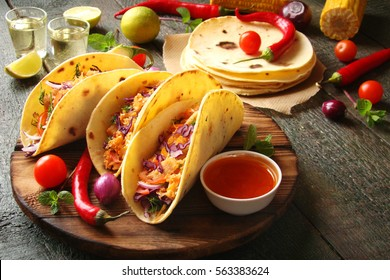 Mexican food tacos, fried chicken, greens, mango, avocado, pepper, red cabbage in tortillas