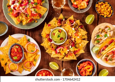 Mexican food variety, shot from the top on a rustic wooden background. Nachos, guacamole, tequila, tacos, a flat lay