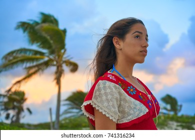 Mexican girl embrodery dress at sunset in Caribbean palm trees