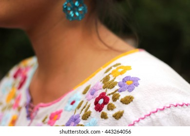 A Mexican girl with traditional folkloric clothes in a rural home backyard