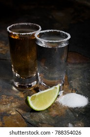 Mexican gold and silver tequila with lime and salt on stone background