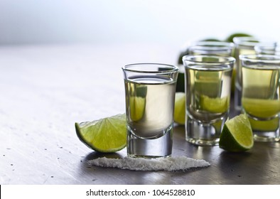 Mexican Gold Tequila in short glasses with lime and salt on old wooden table . Copyspace.