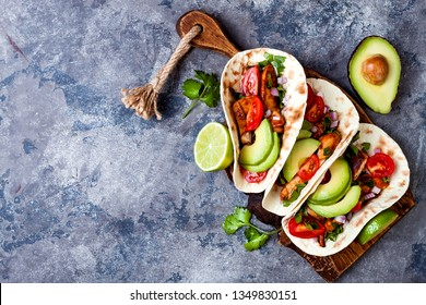 Mexican grilled chicken tacos with avocado, tomato, onion on rustic stone table. Recipe for Cinco de Mayo party. Top view, overhead, flat lay.