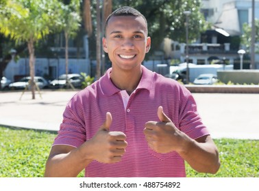Mexican guy in the city showing both thumbs
