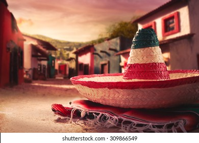 """Mexican hat """"sombrero"""" on a """"serape"""" in a mexican town at sunset"""