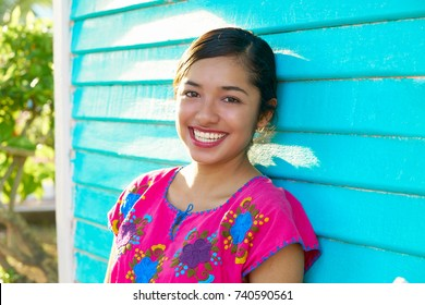 Mexican latin woman with mayan dress smiling in turquoise wall