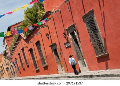 Mexican man passing in front of colorful colonial buildings in Zocalo Street of San Miguel De Allende, Mexico.