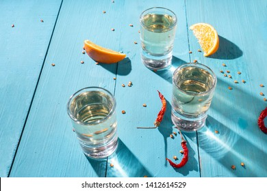 Mexican mezcal shots with slice of orange fruit on wooden background