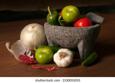 Mexican Molcajete and vegetables to make salsa on a wooden rustic table