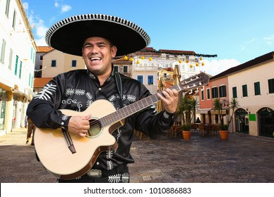 Mexican musician mariachi with guitar on a city street