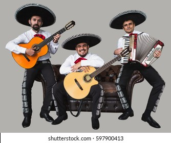 Mexican musicians sit on the old leather sofa. Isolated on gray background.